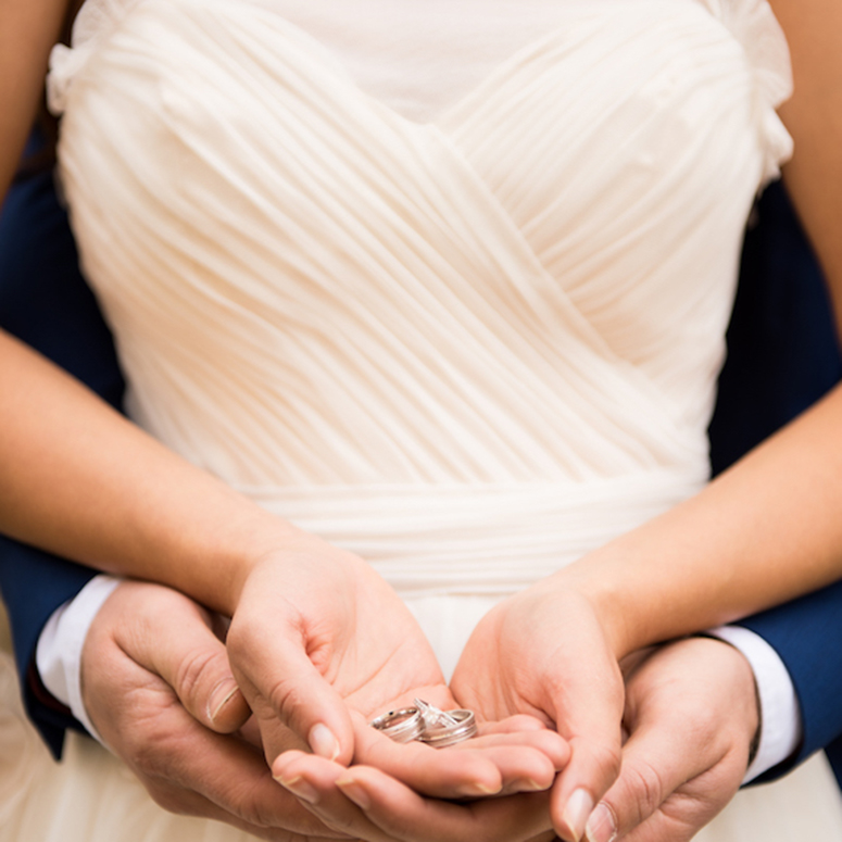 Couple holding their wedding bands in wedding attire