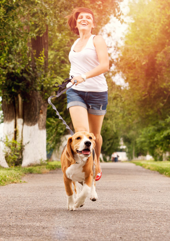 woman running in park with beagle dog