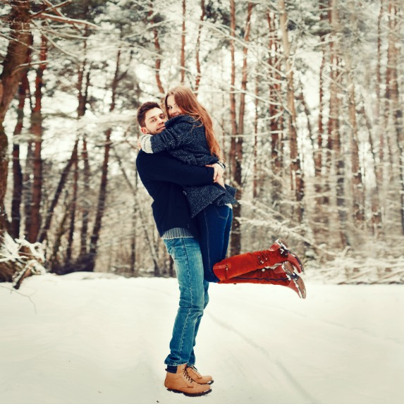 couple hugging in winter forest