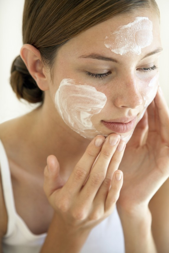 Attractive brunette woman cleansing her face with white face wash.