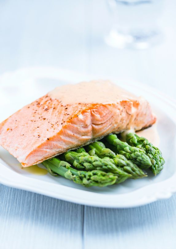 A plate with grilled salmon sitting on top of asparagus.