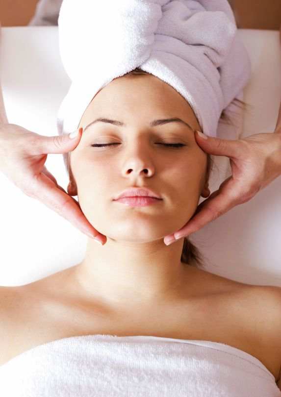 A woman with her hair in a white towel lying down receiving a facial.