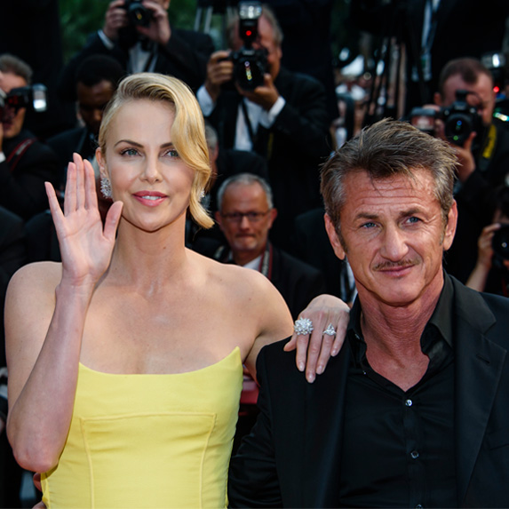 Charlize Theron in a yellow gown waving at the camera with her hand on Sean Penn's shoulder