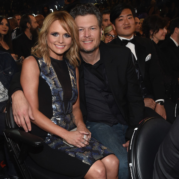 Blake Shelton sitting with his arm around Miranda Lambert at an awards ceremony, and smiling at the cameras