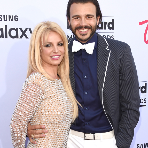 Britney Spears and Charlie Ebersol smiling, and leaning into each other, posing for cameras