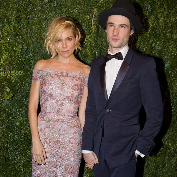 Sienna Miller and Tom Sturridge against a garden wall, holding hands