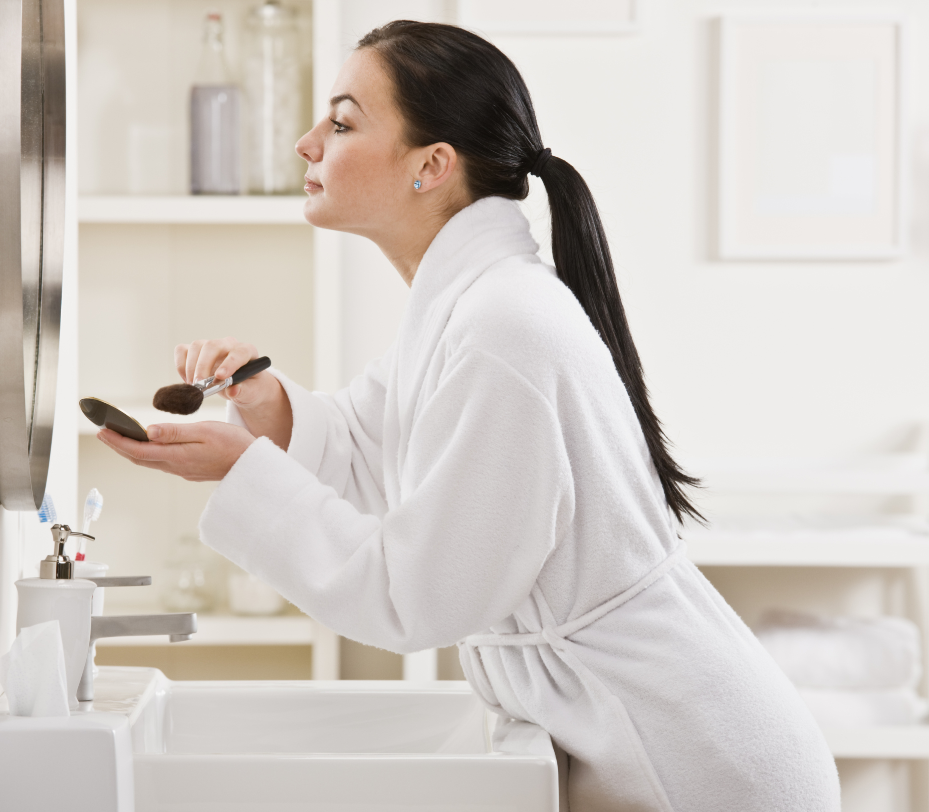Brunette woman in a white bathrobe leaning against the sink applying cosmetics.