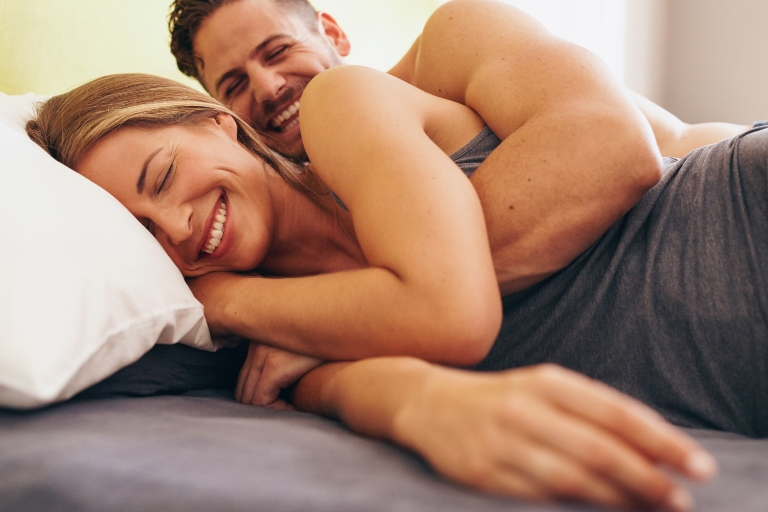 Happy couple cuddling in bed