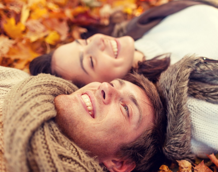 Couple lying in the fall leaves