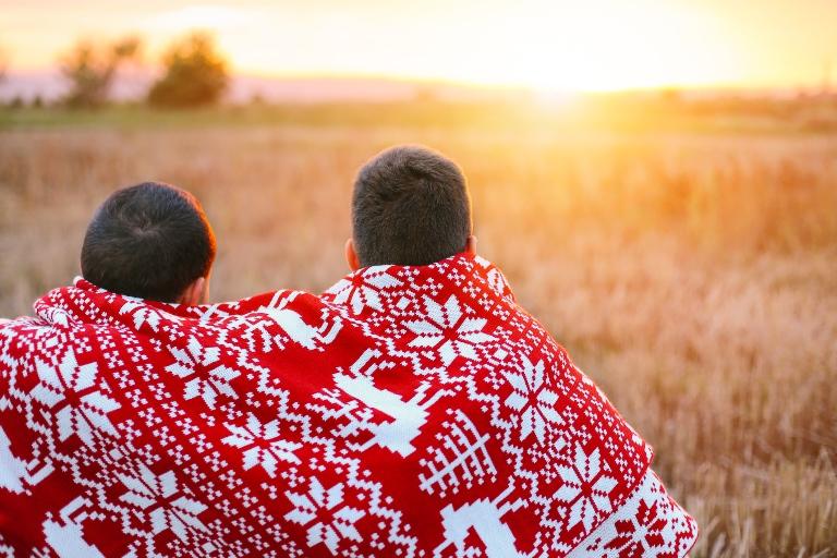 Men snuggled in a blanket