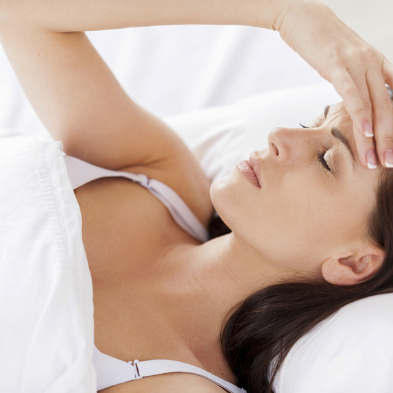 A woman laying down in her bed, eyes closed, with eyes closed and holding her forehead in frustration