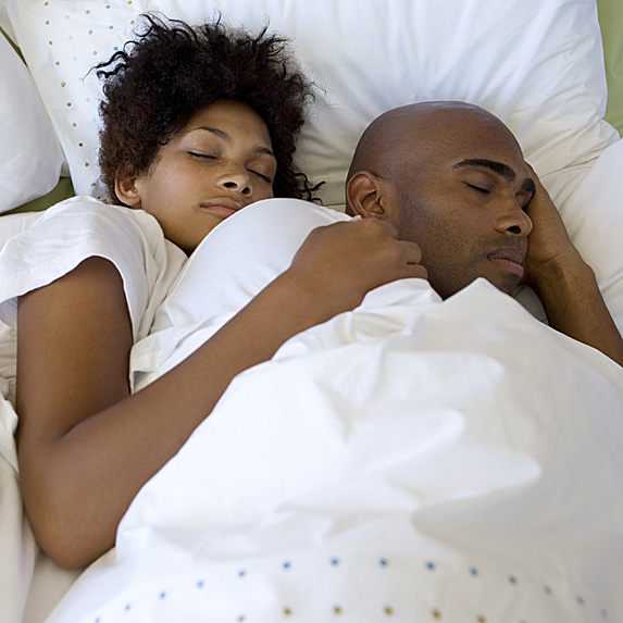 A Black couple sleeping in a bed, with the woman spooning the man