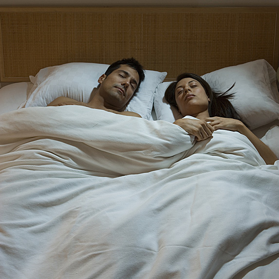 A couple on their back in their bed, sleeping