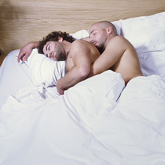 Two men sleeping and spooning