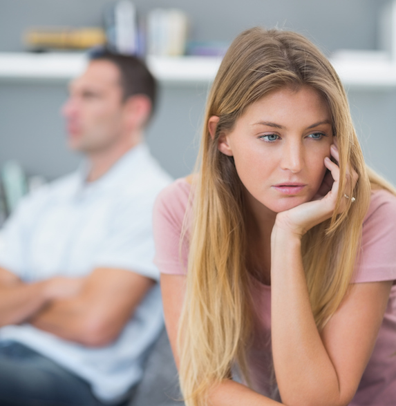 Blonde upset at her boyfriend, he sits with crossed arms