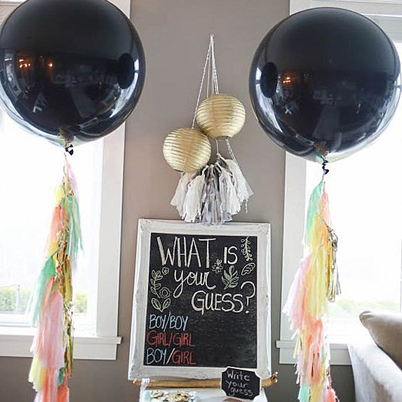 A chalkboard with two big balloons on either side
