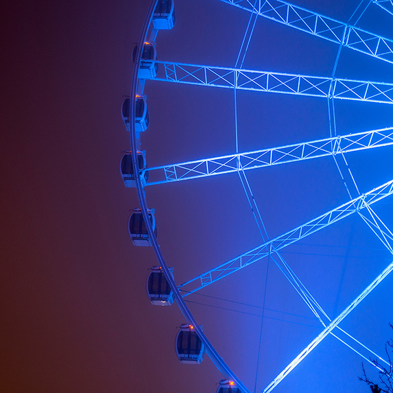 Low angle view of illuminated blue ferris wheel Against Sky