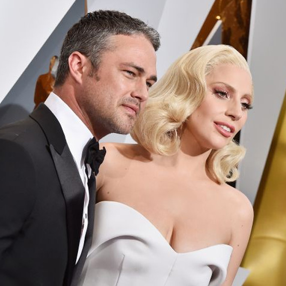 Lady Gaga and Taylor Kinney standing together at a red carpet event