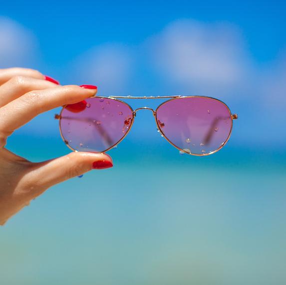 Female hand holding pink sunglasses