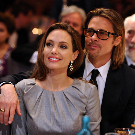 Brad Pitt and Angelina Jolie sitting an awards show together, with Pitt's arm around Jolie