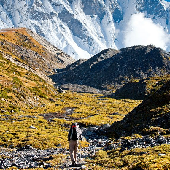 Hiker beneath towering mountains in Nepal in November