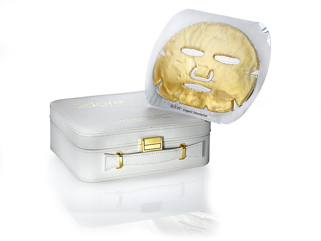 A white box with gold latches and a gold face mask hovering above.