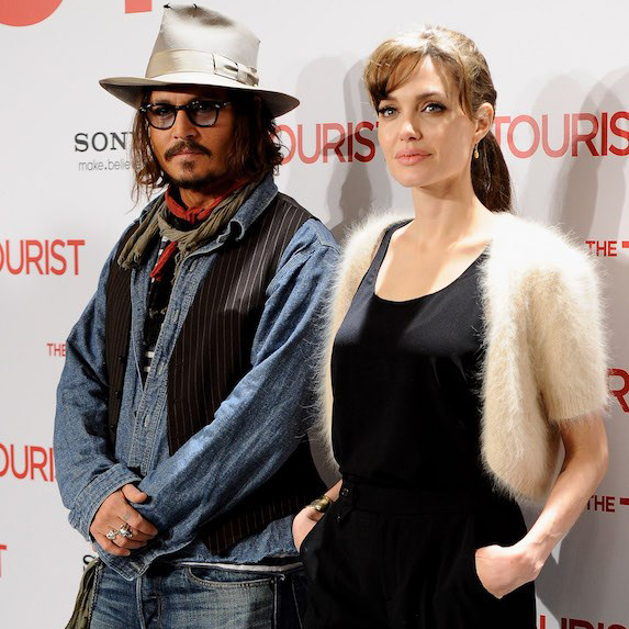 Angelina Jolie and Johnny Depp standing next to each other at a premiere, dressed casually