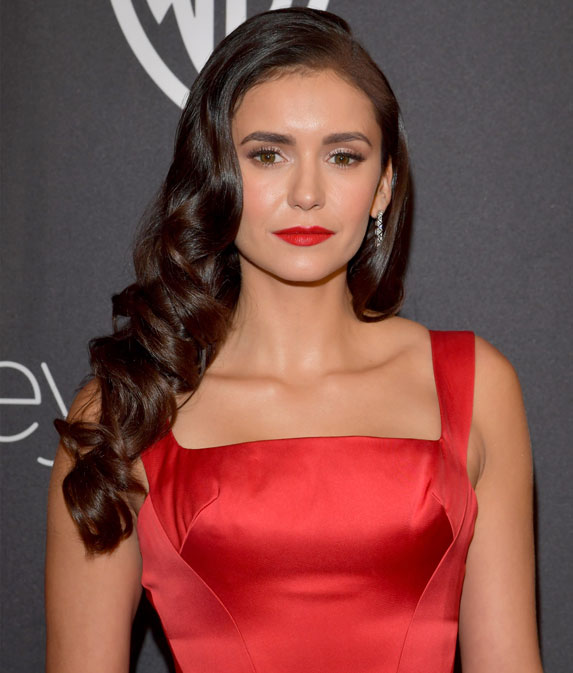 Actress Nina Dobrev wearing a red gown and red lipstick with her long brown hair in waves.