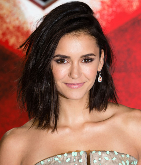 Nina Dobrev with short shoulder length hair flipped to the side.