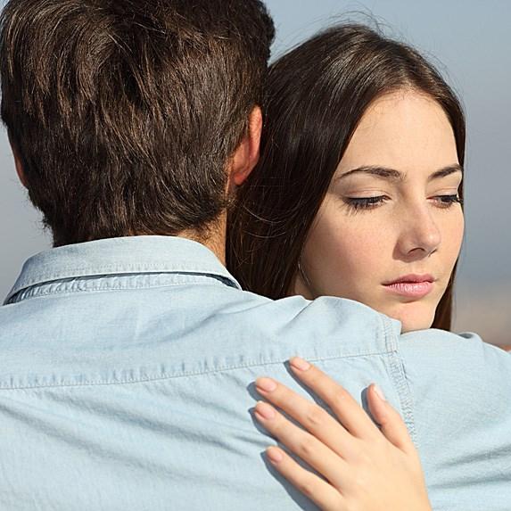 female and male hug while female looks away