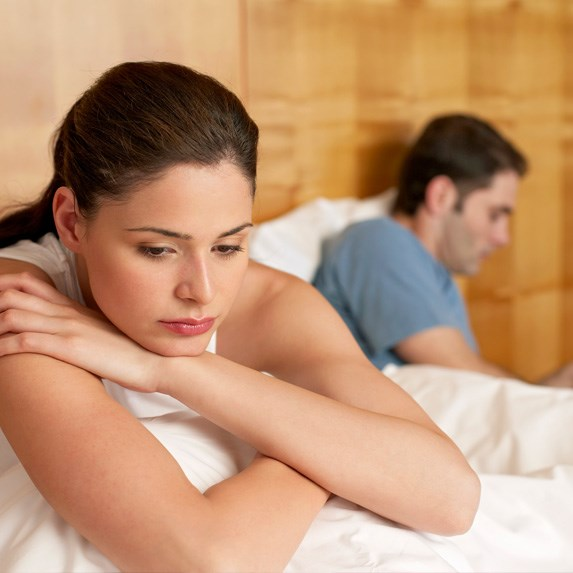 female and male in bed, turned away from one another