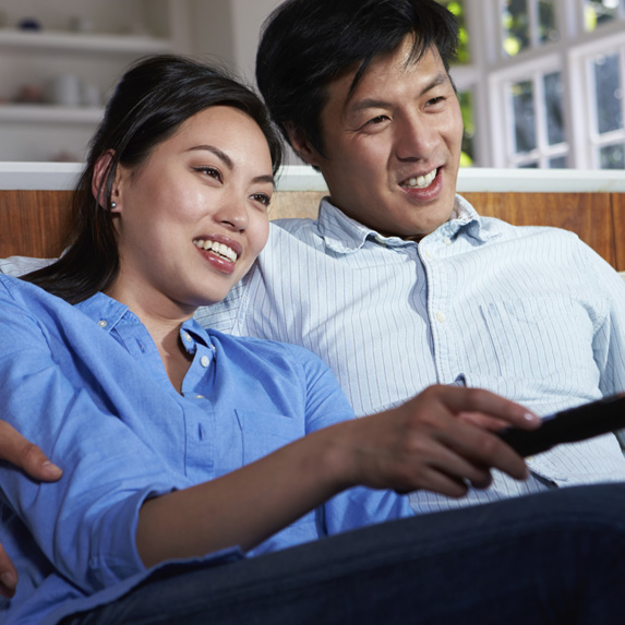 happy man and woman sit on a couch holding a remote