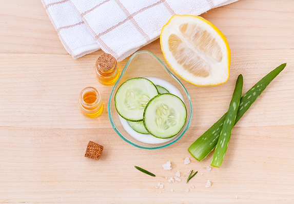 Bird's eye view of Aloe vera stalks, sliced lemon, sliced cucumbers in a bowl of milk and two bottles of essential oils.