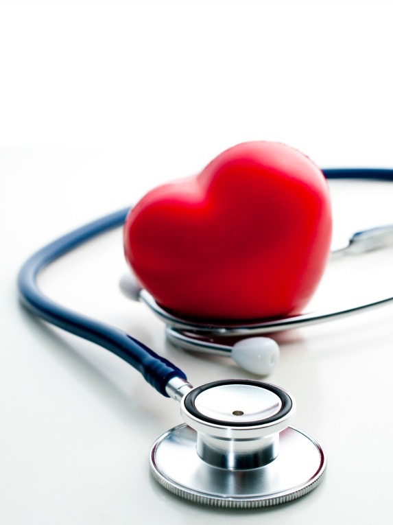 A fake heart sits next to a stethoscope