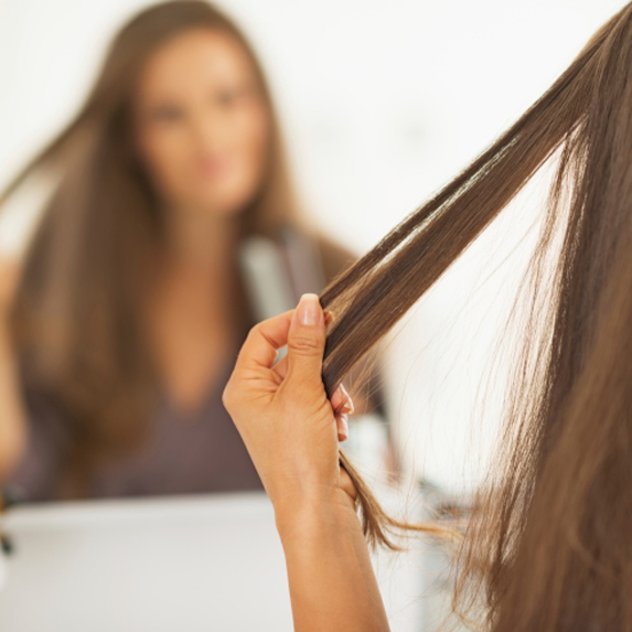 Brunette woman styling hair in the mirror