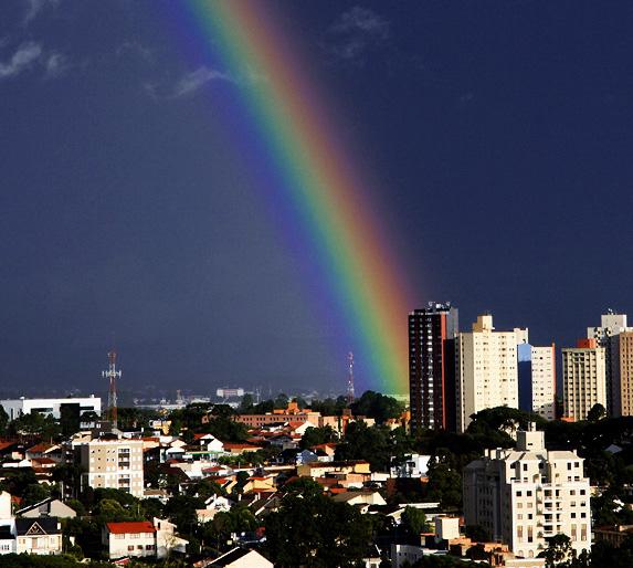 A rainbow beams across a clear blue sky with an urban view of Curitiba, Brazil below