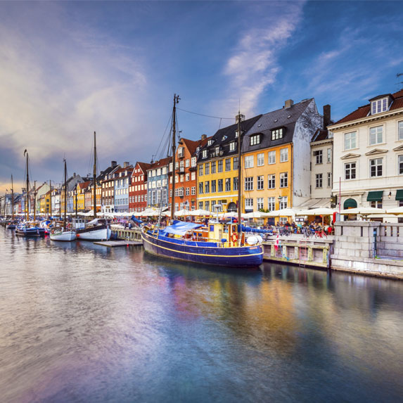 Seaside views on a sunny day toward the colorful boats and homes along the waterfront in Copenhagen, Denmark