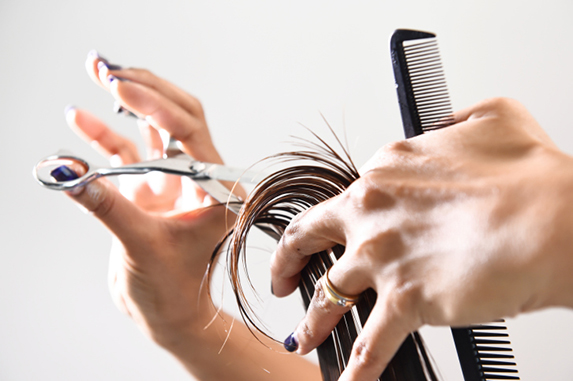 Hands with a comb cutting hair.