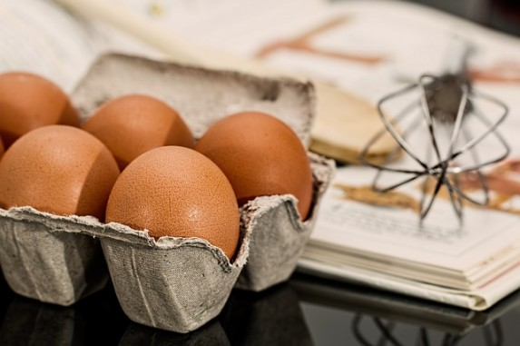 Carton of brown eggs with a whisk and baking tools in the background