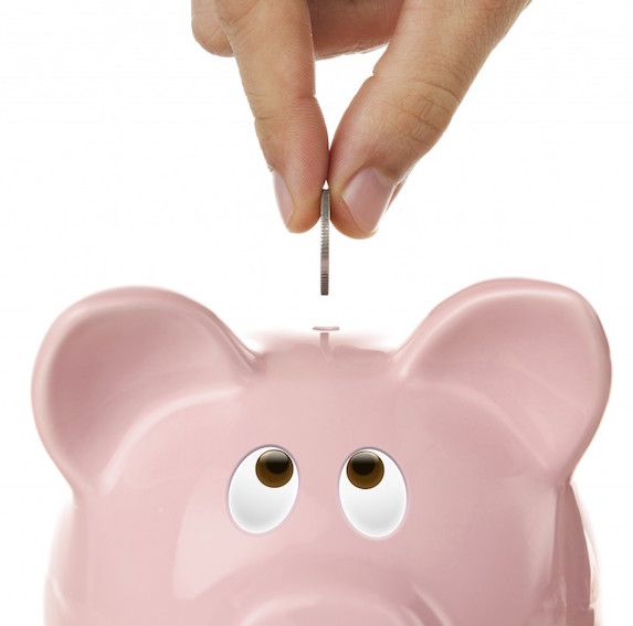 Fingers dropping a coin into the top slot of a pink piggy bank with upward turned eyes