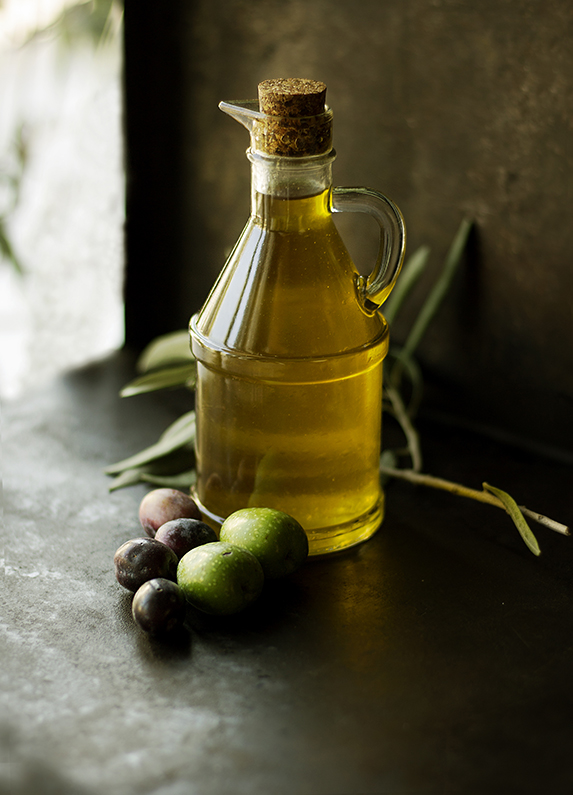A bottle of golden olive oil with fresh olives in front.