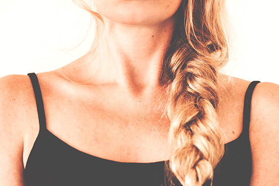 The chin, neck and décolletage of a blond woman wearing a side braid and a black tank top