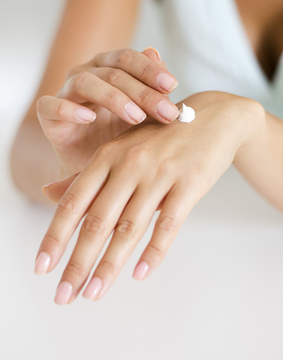 The hands of a woman about to rub face cream onto the back of one of her hands