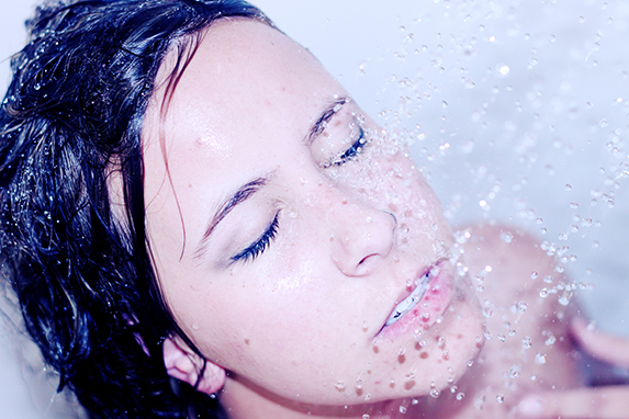 A brunette woman's face with eyes closed under a running shower