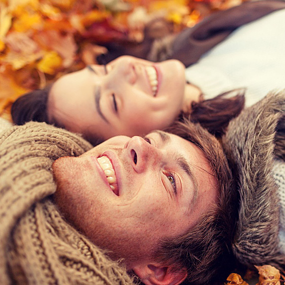 Man and woman lying together in a pile of leaves