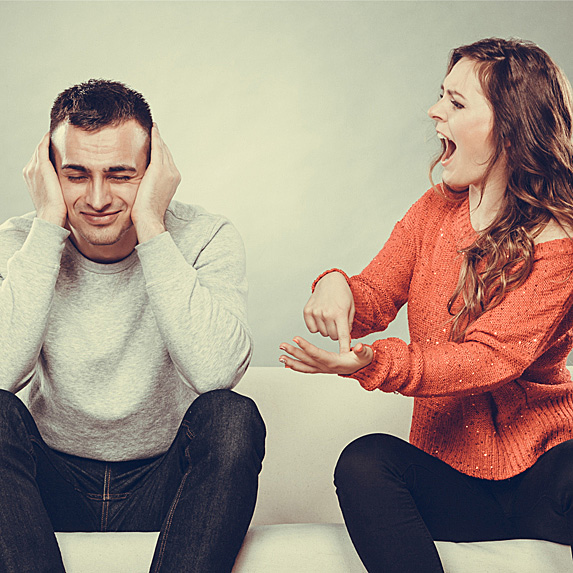 Woman yelling at a man as e holds his head in his hands