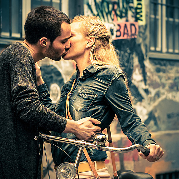 Man and woman passionately kissing on a bike