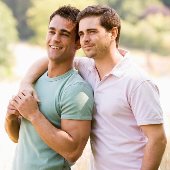 Gay couple in the sunshine with their arms around each other