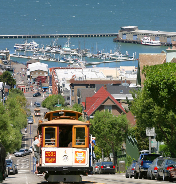 A vintage-looking trolley pulls forward, climbing a steep hill lined with cars and homes with a view of the seaport and boats in the harbor down below