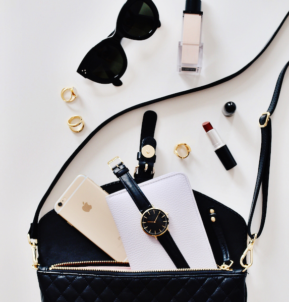 Small quilted black purse lies on a table with the contents (sunglasses, perfume, makeup, jewelry, phone) spilled out